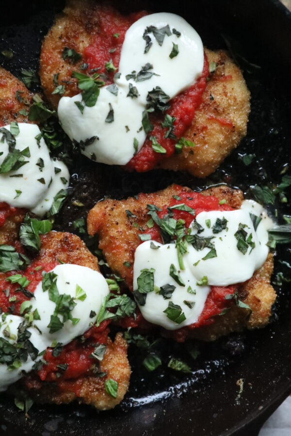 Closeup of Paleo Chicken Parmesan topped with Pomi tomatoes, melted mozzorella and fresh basil