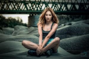 Girl auf Steinen mit Brücke