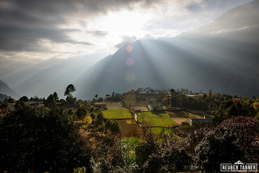 The sun bursts from behind clouds, above the Himalayas, Nepal. (Reuben Tabner/© Reuben Tabner)