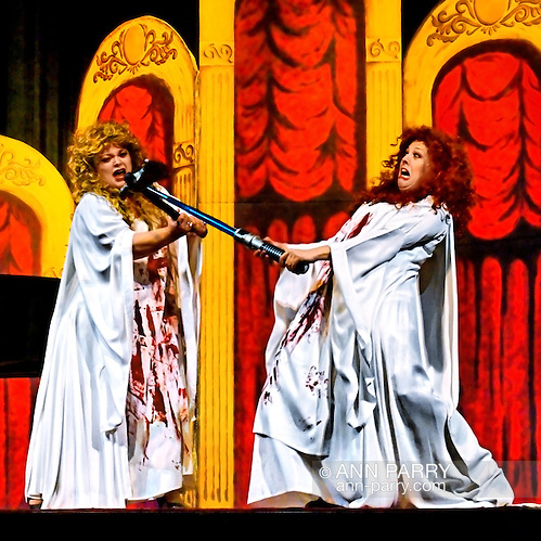 """MERRICK, NY - February 21: Duelling Divas concert with sopranos Birgit Firavante and Wendy Reynolds and pianist Heather Coltman in bloody fight, one using sword to block hatchet swung at her face, in Mad scene from Donizetti's """"Lucia di Lammermoor"""" in comic opera concert presented by Merrick Bellmore Community Concert Association. (© 2010 Ann Parry/Ann-Parry.com)"""