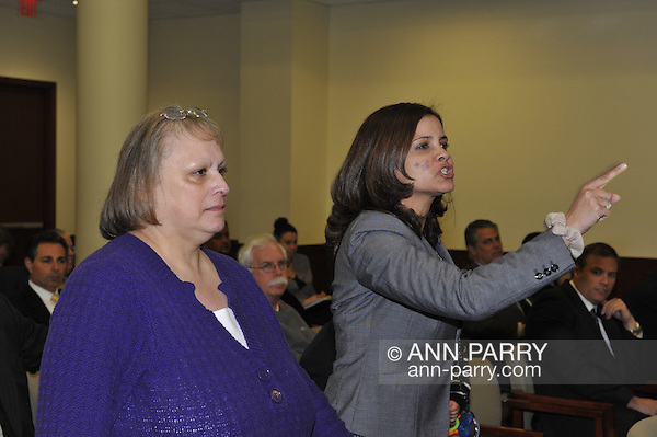 Nassau County Legislature, controlled by Republicans, votes along party lines to consolidate 8 police precincts into 4, on Monday, March 5, 2012, at Mineola, New York, USA. Milagros Vicente (right, pointing finger), a North Valley Stream resident, is one of those shouting out in audience after a Yes vote by a legislator. (Ann Parry/Ann Parry, ann-parry.com)