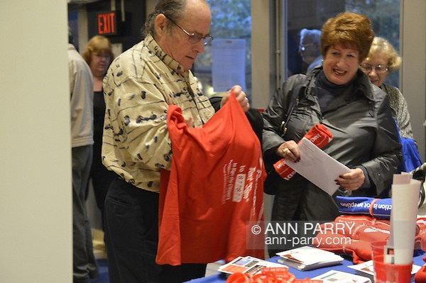 "Oct. 15, 2012 - Hempstead, New York, U.S. - Man attending Simpson and Bowles event at Hofstra puts on red shirt that Fix the Debt Campaign gives free to anyone who puts in on right there in lobby and wears it to event at Hofstra University's John Cranford Adams Playouse., The campaign's co-founders, Simpson and Bowles, speak in the auditorium about ?America's Debt and Deficit Crisis: Issues and Solutions.? This event with the co-chairmen of the National Commission on Fiscal Responsibility and Reform, and co-leaders of Simpson-Bowles non-partisan U.S. fiscal debt reduction plan, was part of ""Debate 2012 Pride Politics and Policy"" a series of events leading up to when Hofstra hosts the 2nd Presidential Debate between Obama and M. Romney, the next night, October 16, 2012, in a Town Meeting format. (Ann Parry/Ann Parry, ann-parry.com)"