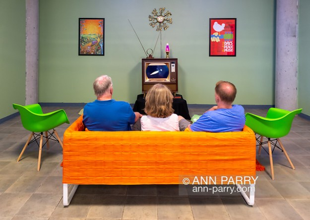 Garden City, New York, U.S. July 25, 2019. L-R, father BILL WALSH and mother KATE WALSH of Port Jefferson, and son KEVIN WALSH of Miller Place, sit on sofa in American 60s style living room, while watching CBS Apollo 11 news coverage on a tube TV set, with simulation of July 20, 1969, lunar module Moon Landing. The Cradle of Aviation Museum set was for its recent Apollo 11 Countdown on the 50th Anniversary of man first walking on the moon. (© 2019 Ann Parry/Ann-Parry.com)