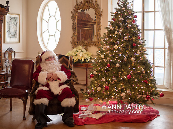 Old Westbury, New York, USA. December 17, 2017. Santa sits ready for visitors next to a Christmas tree on second floor of Westbury House at Old Westbury Gardens museum during snowy winter holiday weekend. (© 2017 Ann Parry/Ann-Parry.com)