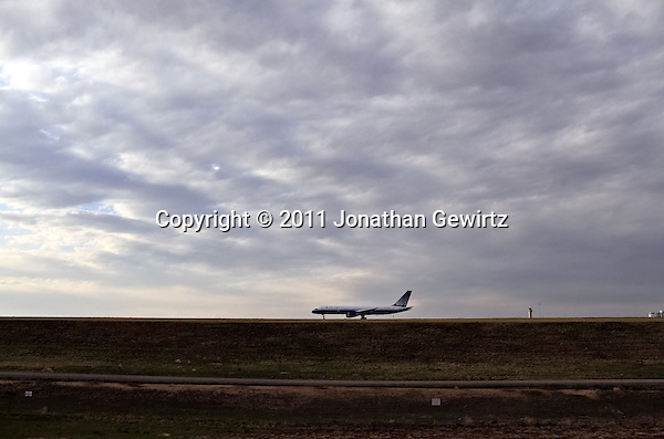 A United Airlines Boeing jetliner on the taxiway at Denver International Airport is silhouetted against a cloudy sky. (Jonathan Gewirtz)