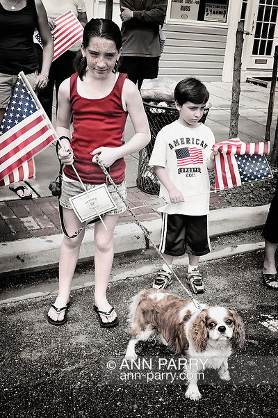 Merrick, New York, U.S. - May 30, 2011 - Freckled girl with dog, and young boy at Memorial Day Parade, Merrick, New York, USA, on May 30, 2011. Tinted and textured noise added for vintage effect. (Ann E Parry/Ann Parry, Ann-Parry.com)