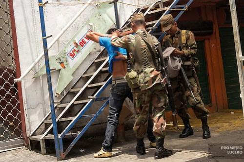 Un soldado inspecciona la espalda de un joven en busca de tatuajes mientras otro revisa su mochila en las calles céntricas de San Salvador.. San Salvador, mayo de 2012. (Foto: Prometeo Lucero) (Prometeo Lucero)