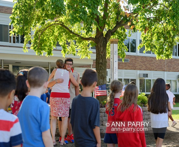 orth Merrick, New York, U.S. September 11, 2019. At Park Avenue School, a teacher hugs NICHOLAS CARRANO, 15, of Merrick, a member of Boy Scout Troop 123 , as her students walk around the 9/11 Memorial Garden on their way back into school after 9/11 ceremony, on 18th Anniversary of terrorist attacks Sept. 11, 2001. (© 2019 Ann Parry/Ann-Parry.com)