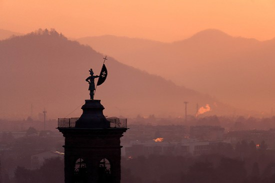 Statue on top of bell tower at Church of Sant'Alessandro della Croce silhouetted against sunrise, Bergamo, Italy (Brad Mitchell Photography)