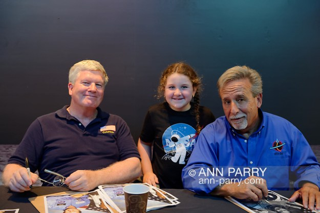 Garden City, NY, U.S. July 20, 2019. L-R, NASA Space Shuttle astronaut BILL SHEPHERD, ADRIANA IACONO, 6, of Franklin Square, and Space Shuttle astronaut CHARLIE CAMARDA, are at the astronaut autographing table, at the Moon Fest Apollo at 50 Countdown Celebration at Cradle of Aviation Museum in Long Island. (© 2019 Ann Parry/Ann-Parry.com)