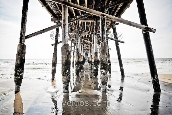 HDR photo of Newport Pier underside support posts on Balboa Peninsula in Newport Beach California. Newport Beach is a coastal community along the Pacific Ocean in Orange County California. (Photographer: Paul Velgos)