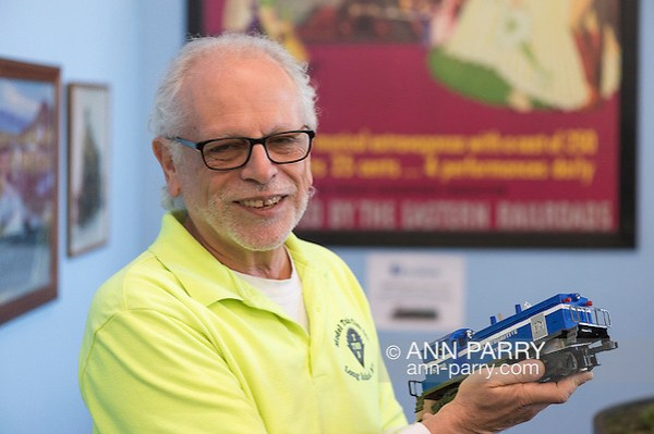 Farmingdale, New York, USA. November 26, 2016. BAKE TURNER, of Melville, holds a blue Electromotivee Division EMD model train engine at the Train Masters of Babylon TMB Model Train Club's Open House. Visitors enjoyed a 4000 square foot O Gauge model railroad with 10 trains running on 19 scale miles of track and an underground subway system. Watching O Scale model trains traveling on tracks through various elaborate scenes was family fun, free and open to the public, during the long Thanksgiving holiday weekend. (Ann Parry/Ann Parry, ann-parry.com)