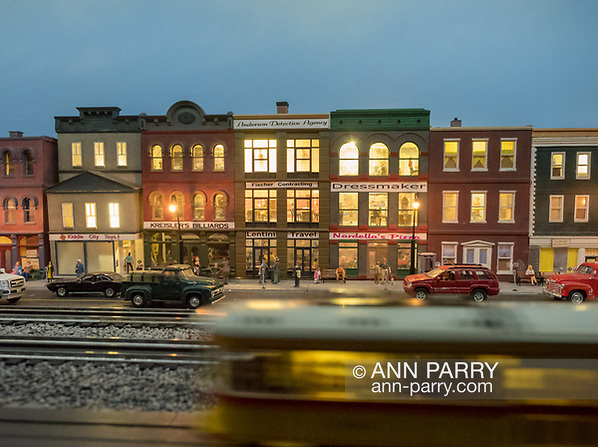 Farmingdale, New York, USA. January 21, 2018. Trolley model train speeds by old-fashioned downtown night scene at Babylon Train Masters Open House at TMB Headquarters (Ann Parry/Ann Parry, ann-parry.com)