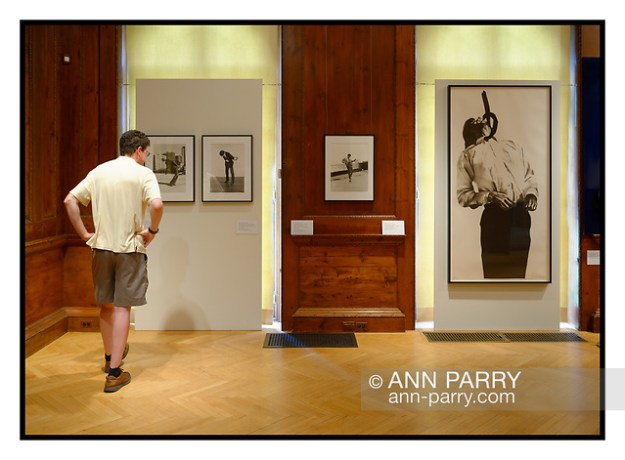 "Roslyn, New York, U.S. July 7, 2019. Visitor looks at artwork from Men in the Cities series by Robert Longo (b. 1953). From L-R, the first 3 are Untitled, analog silver gelatin prints, 20 x 16 inches; at extreme right is ""Men in the Cities: Eric,"" (1983), lithograph on rag paper, 71 1/2 x 35 7/8 inches. (© 2019 Ann Parry/Ann-Parry.com)"