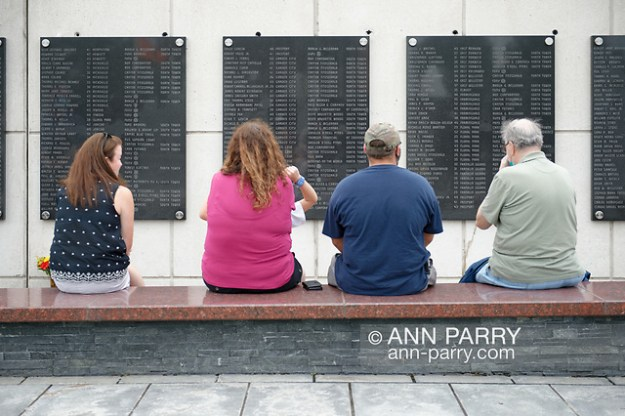 East Meadow, New York, U.S. September 10, 2020. At far left, TRICIA DEAN, widow of William T. Dean, of Floral Park, who died during terrorist attack on Twin Towers, sits at Nassau County Eisenhower Park September 11, 2001 Memorial, on bench across from plaque where her husband's name is listed among 348 county residents killed by the attacks. (© 2020 Ann Parry/AnnParry.com)