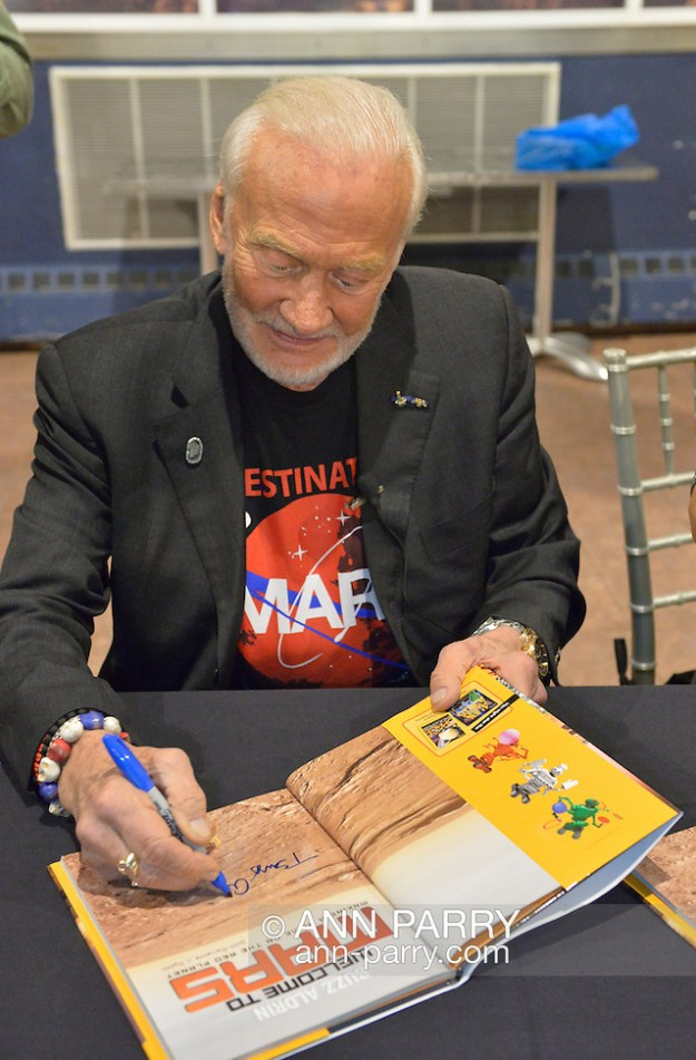 Garden City, New York, USA. October 23, 2015. Former NASA astronaut Edwin BUZZ ALDRIN autographs his new book Welcome to Mars: Making a Home on the Red Planet, a National Geographic Kids book for Middle Grades. Before that, Aldrin discussed his childhood, experiences in space, and importance of exploring Mars, in the jetBlue Sky Theater Planetarium at Long Island's Cradle of Aviation Museum. Aldrin is wearing his Destination MARS shirt. On the 1969 Apollo 11 mission, Aldrin was the second person ever to walk on the Moon, and his first trip to space was the1966 Gemini 12. (© 2015 Ann Parry/Ann-Parry.com)