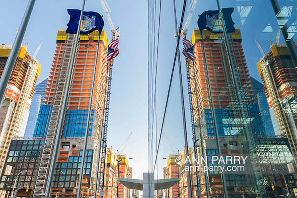 Manhattan, New York, USA. April 12, 2017. Nearby construction at corner or 11th Avenue and W 35th Street is reflected on exterior glass walls of Javits Center on early spring evening. (Ann Parry/annparry.com)