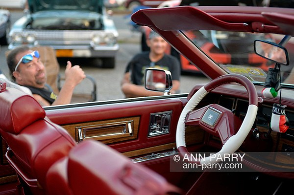 Bellmore, New York, USA. August 24, 2018. Owner Frankie D'Amore, of Levittown sits next to his 1984 white Cadillac El Dorado Biarritz convertible with a particularly fitting license plate number BAC2D80S, at Bellmore Friday Night Car Show. (Ann Parry/Ann Parry, ann-parry.com)