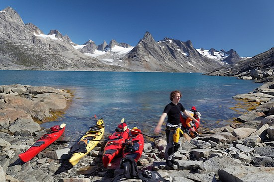 Sea kayakers taking break on beach, Ikaasatsivaq Fjord, Ammassalik Island, East Greenland (Brad Mitchell)
