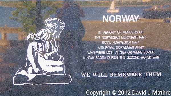 Norway Memorial in Halifax, Nova Scotia. Image taken with a Leica V-Lux 30 camera (ISO 125, 13.6 mm, f/4.7, 1/80 sec). The image includes the reflection of the photographer, Halifax Harbor, and a sailboat. (David J Mathre)