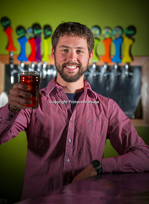 Ben Mills, owner of Fossil Cover Brewing Company holds a glass of beer while standing in his bar on Friday, March 20, 2014, in Fayetteville, Arkansas. Photo by Beth Hall (Beth Hall)