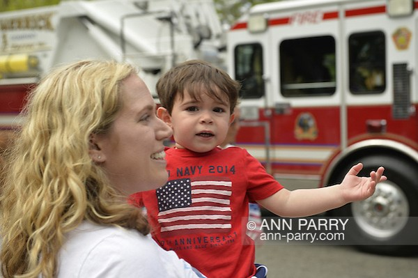 Merrick, New York, U.S. - May 26, 2014 - Mother holds her 2-year-old son who is pointing to a Fire Engine in the Merrick Memorial Day Parade, hosted by American Legion Post 1282 of Merrick, honoring those who died in war while serving in the United States military. (Ann Parry/Ann Parry, ann-parry.com)