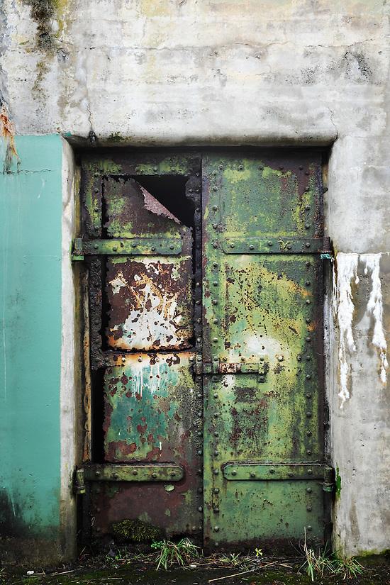 Closed rusty green steel door on concrete bunker tunnel, Artillery Hill, Fort Warden State Park, Port Townsend, Washington, USA (Brad Mitchell)