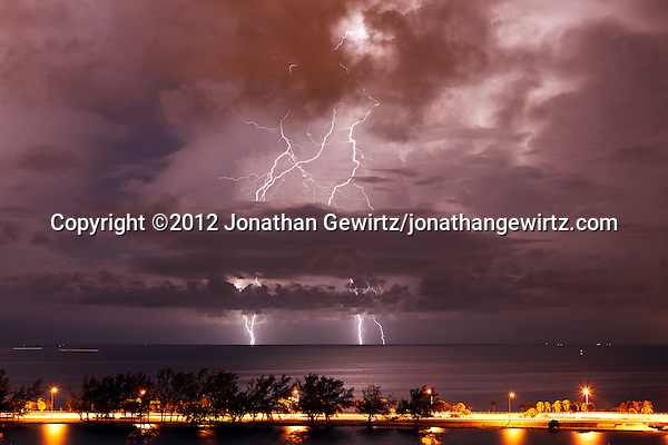 Cloud-to-ground lightning strikes the southern side of Biscayne Bay during a nocturnal thunderstorm in Miami, Florida. Rickenbacker Causeway is visible in the foreground. (© 2012 Jonathan Gewirtz / jonathan@gewirtz.net)