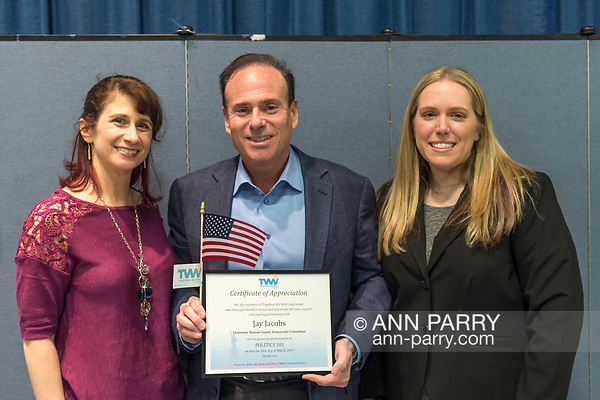 Wyandanch, New York, USA. March 26, 2017. At center, JAY JACOBS, Chairman of Nassau County Democratic Committee, holds Certificate of Appreciation and American Flag presented by, (L) BETH McMANUS, and (R) SUE MOLLER, two administrators of Together We Will Long Island. Jacobs spoke at Politics 101 event, the first of a series of activist training workshops for members of TWW LI, the L.I. affiliate of TWW. (Ann Parry/Ann Parry, ann-parry.com)