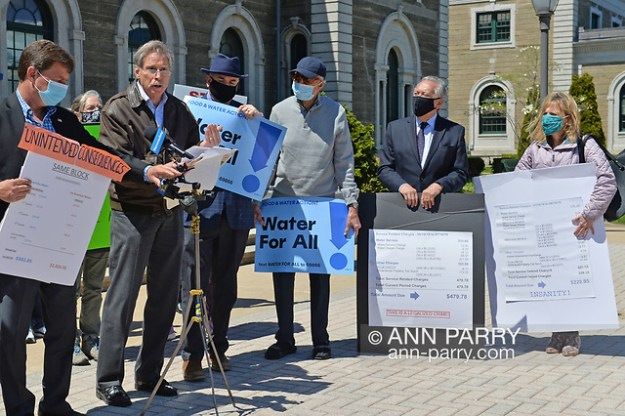 """Mineola, NY, USA. April 26, 2021. L-R, DAVE DENENBERG, Co-Director of CAWS; LLOYD NADEL (speaking at mics) attorney for Glen Head-Glenwood Landing Civic Council; ERIC WELTMAN, Senior Organizer for Food & Water Watch and Food & Water Action; (activist); GEORGE POMBAR, Pres. of GH/GL Civic Council; and AGATHA NADEL, Director of NSCC,  speak at rally. Faced with a 26% rate increase from New York American Water going into effect May 1, 2021, activists and residents who are NYAW customers rally. (© 2021 Ann Parry/AnnParry.com)"