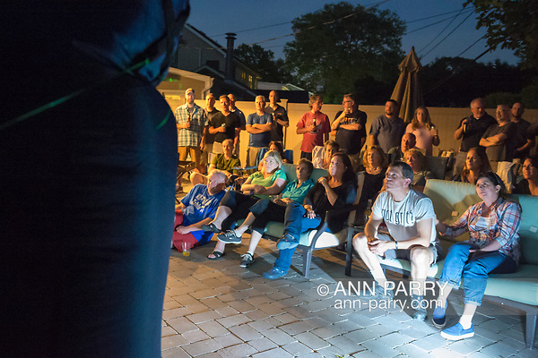 "Merrick, New York, USA. 11th June 2017. ""American Grit"" TV contestant CHRIS EDOM (at bottom right, wearing white GOT GRIT? T-shirt), 48, sits with his wife, JOAN EDOM, of Merrick, as they host backyard Viewing Party for Season 2 premiere. Edom family and neighbors watched Episode 1 of FOX network reality television series that Sunday night on a big screen (at left) outdoors. Edom was last contestant picked for a team. (Ann Parry/Ann Parry, ann-parry.com)"