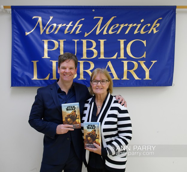 Merrick, New York, U.S. Dec. 20, 2019. L-R, Author KEVIN SHINICK and his mother LOUISE SHINICK, both holding his novel, pose at North Merrick Public Library banner during book signing for his STAR WARS: FORCE COLLECTOR, on Nassau County Force Collector Day. (© 2019 Ann Parry/Ann-Parry.com)