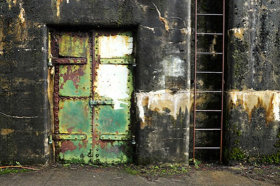 Closed rusty green steel door and ladder on concrete bunker tunnel, Artillery Hill, Fort Warden State Park, Port Townsend, Washington, USA (Brad Mitchell)