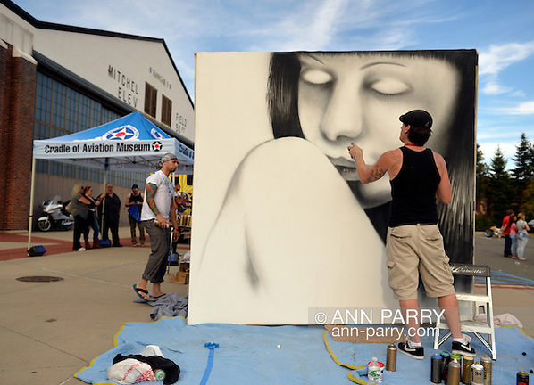 Garden City, New York, USA. September 14, 2014. SEAN GRIFFEN, aka NME, of Freeport, is a graffiti artist creating an outdoor mural of a girl, at the United Ink Flight 914 tattoo convention at the Cradle of Aviation museum of Long Island. (Ann Parry/Ann Parry, ann-parry.com)