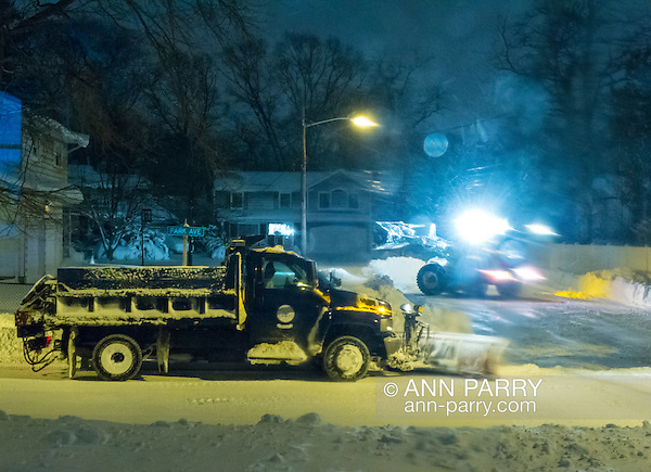 Merrick, New York, USA. 24rd January 2016. Two Town of Hempstead snowplows, a small one plowing out a cul de sac, dead end side street, and a large plow on the bigger road leading to it, are clearing roads while Blizzard Jonas continues to bring dangerous snow and gusting winds to Long Island. Governor Cuomo banned travel, shutting down L.I.'s roads and railroads, due to hazardous conditions, and the winter Storm of 2016 has already dropped about two feet of snow on the south shore town. (Ann Parry/Ann Parry, ann-parry.com)