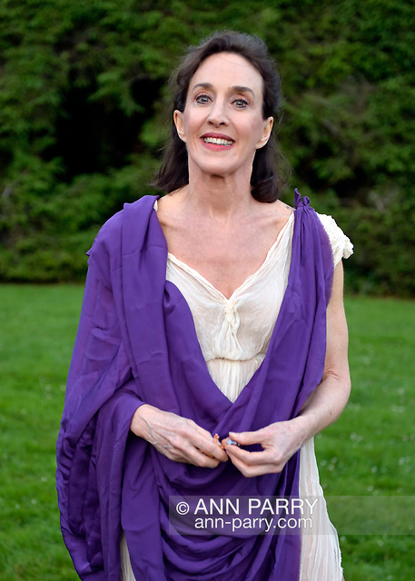 """Old Westbury, New York, U.S. - June 21, 2014 - Lori Belilove & The Isadora Duncan Dance Company dances modern dance in Greek tunics throughout the gardens during the Midsummer Night event at the historic Long Island Gold Coast estate of Old Westbury Gardens. Ms. Belilove is wearing a Greek white tunic and purple over-scarf. (© 2014 Ann Parry/AnnParry.com)"