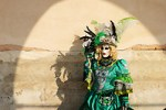 Woman dressed in traditional mask and costume for Venice Carnival standing under arch at Doge's Palace, Piazza San Marco, Venice, Veneto, Italy (Brad Mitchell Photography)