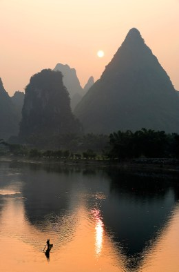 A man paddles a bamboo raft on the Lijiang River under the rising sun and karst mountains, Yangshuo, Guanxi, China (Brad Mitchell/Brad Mitchell Photography)