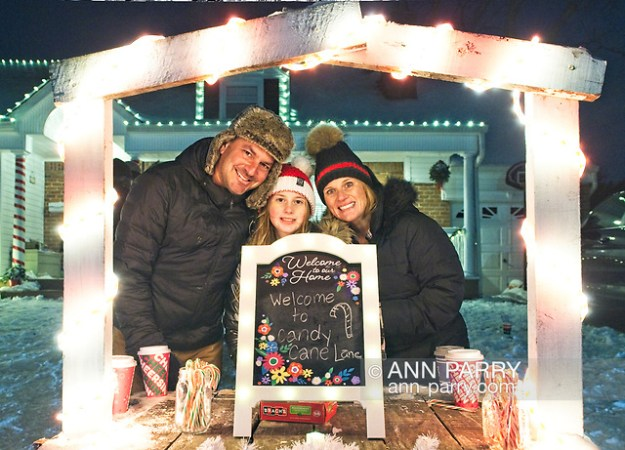"""North Merrick, NY, U.S. Dec. 19, 2020. L-R, JOSH MACK, JESSICA MACK, and daughter CALLEIGH MACK, 10, are posing at their Candy Cane Lane candy stand in front of their home during Community Holiday Tree Walk. (© 2020 Ann Parry/Ann-Parry.com)"