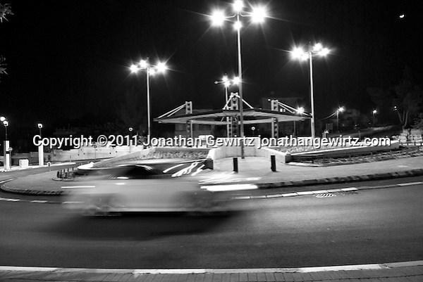 A car drives through a Jerusalem traffic circle at night (black & white). (Jonathan Gewirtz)