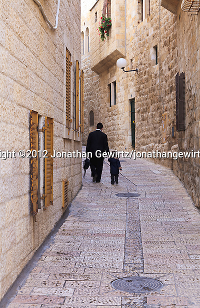 A father walks with his young child on a narrow street in the Jewish Quarter of the Old City of Jerusalem. (© 2012 Jonathan Gewirtz / jonathan@gewirtz.net)