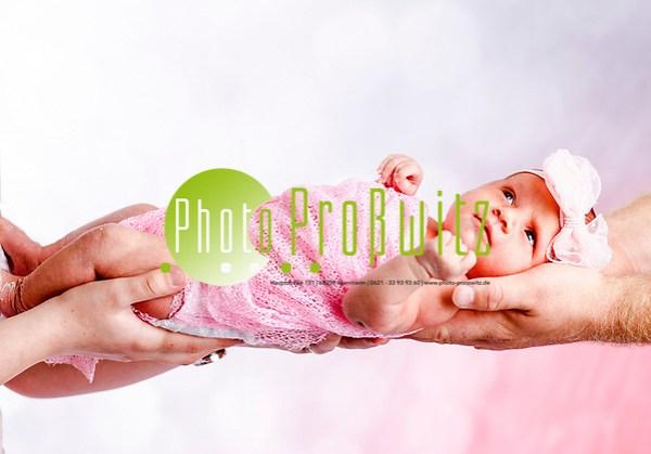 Fotoshooting mit Baby, zart auf dem Arm