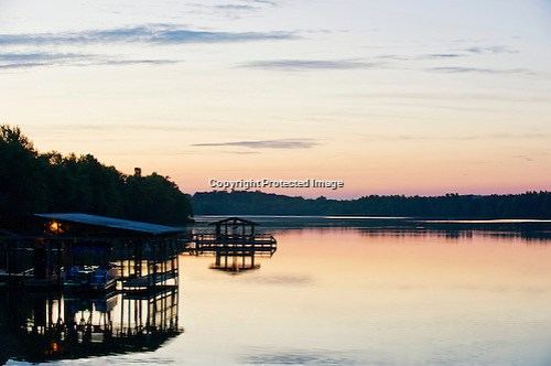 Boat docks are silhouetted against the rising sun on Lake Fayetteville in Fayetteville, Arkansas. (Beth Hall)