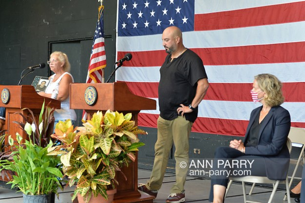 East Meadow, New York, U.S. September 10, 2020. SUSAN HUTCHINS, at far left podium, holds up photo of her son Kevin Colbert, who died after a plane hit South Tower on September 11, 2001. Nassau County Executive LAURA CURRAN sits at far right, as county commemorated 19th anniversary of September 11 terrorist attacks with Remembrance Ceremony at Eisenhower Park.