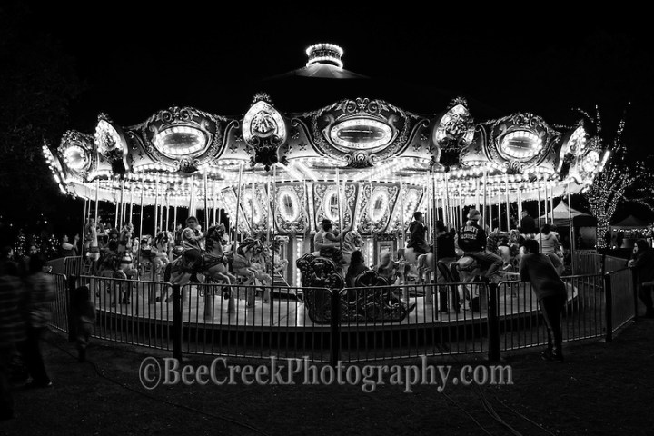 We capture cityscape image late one night of this carousel ride at a Christmas festival in the city and we like how eerie it looked in Black and White.  It had this hauntingly eerie look almost like what you would of see on one of those old television show like the  twilight zone  You see a few children and teenager riding the horses and a few standing around watching but it closing time so this is the last ride. (Tod Grubbs & Cynthia Hestand)