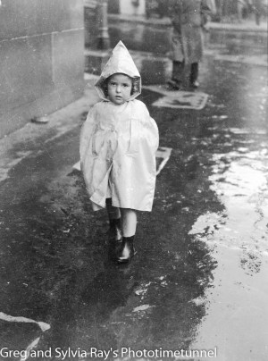 Child in a raincoat in Newcastle, circa 1940s.