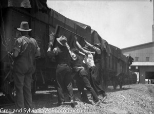 Workers at the side of railway wheat trucks at Newcastle's grain silos, December 5, 1938.