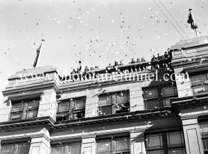 Confetti raining from the Newcastle Herald building. Celebrations in Newcastle, NSW, for the end of World War 2, August 15, 1945.