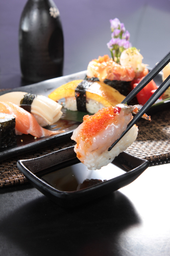 Use chopsticks to pick up red shrimp and crab roe sushi with soy sauce