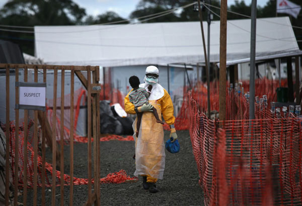 Series title: Ebola Crisis Overwhelms Liberian Capital; Image title: Suspect Image description: An MSF health worker in protective clothing carries a sick girl at an Ebola treatment center. Copyright: © John Moore / Getty Images, US, L'Iris d'Or,, 2015 Sony World Photography Awards
